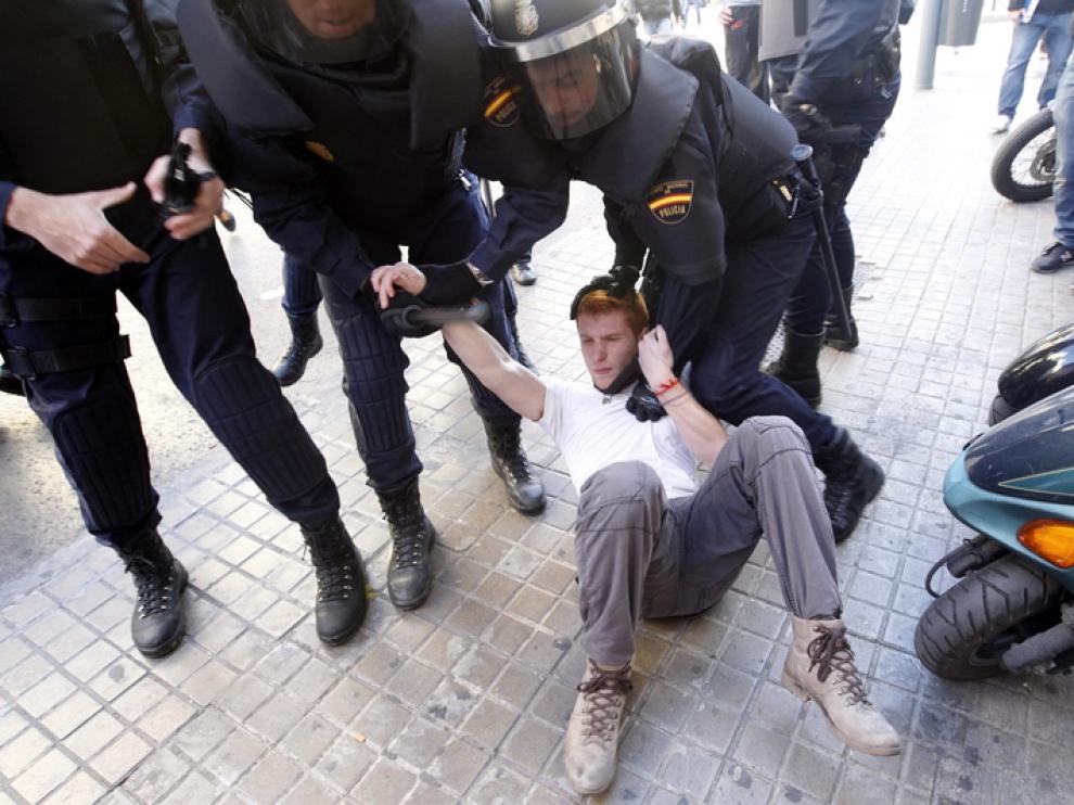 La policía custodia a un manifestante durante las protestas de Valencia.