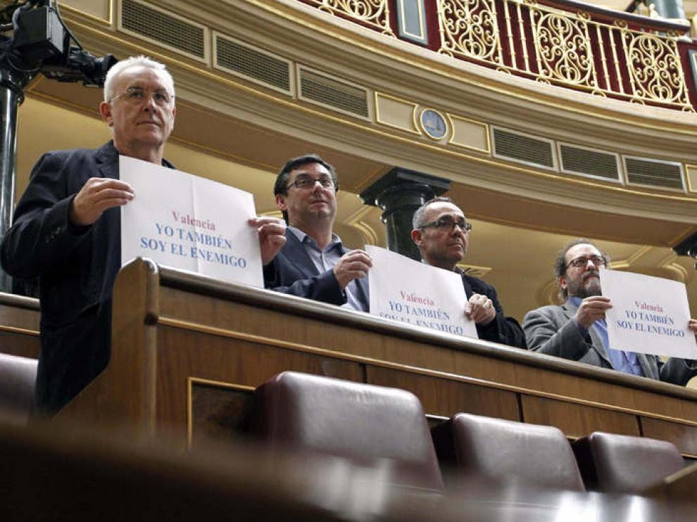 """El diputado de IU, Cayo Lara, sotiene en el Congreso una pancarta que dice """"Yo también soy el enemigo"""""""