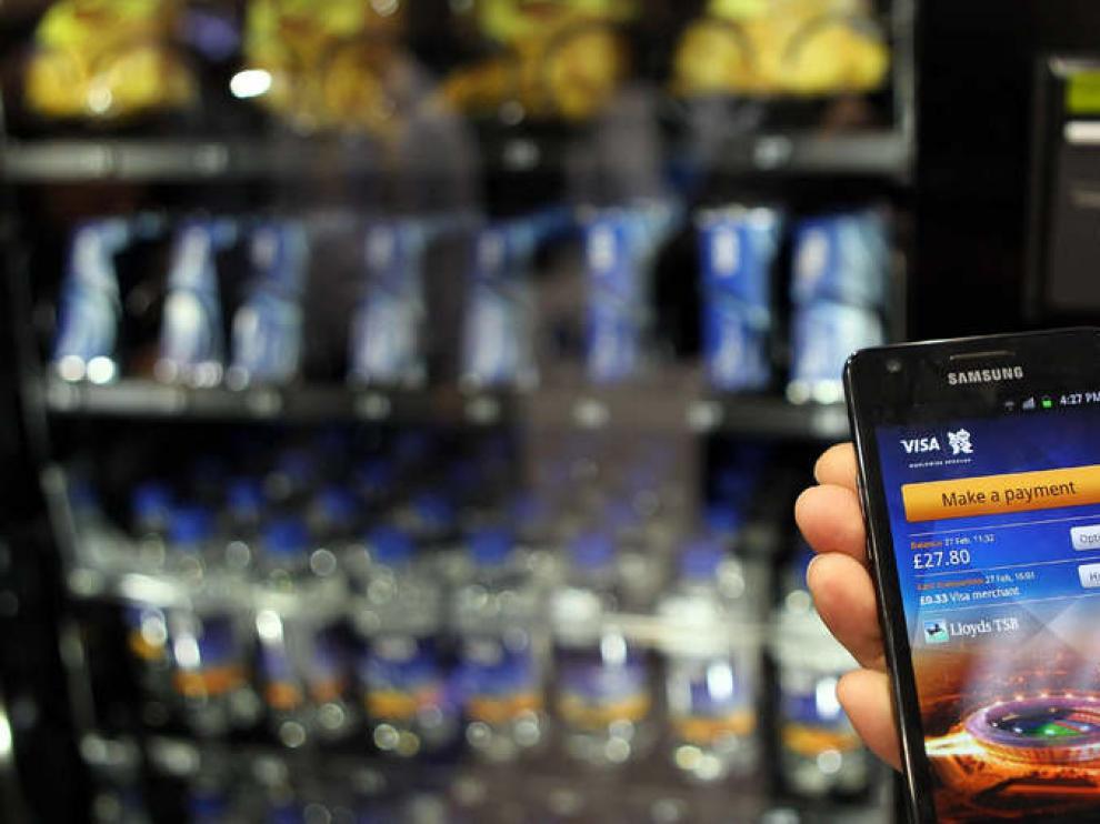 Un empleado muestra cómo comprar a través del 'smartphone' con una cuenta VISA.