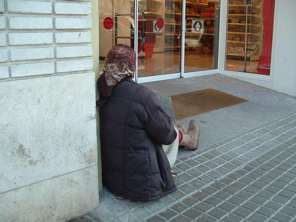 Una mujer pide limosna en la puerta de un supermercado de Huesca