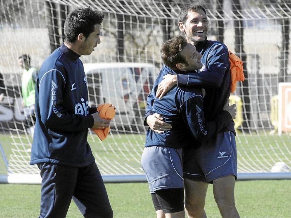 Josetxo se abraza con Llamas ante la mirada de Jorge Larena durante el entrenamiento de ayer en el IES Pirámide.