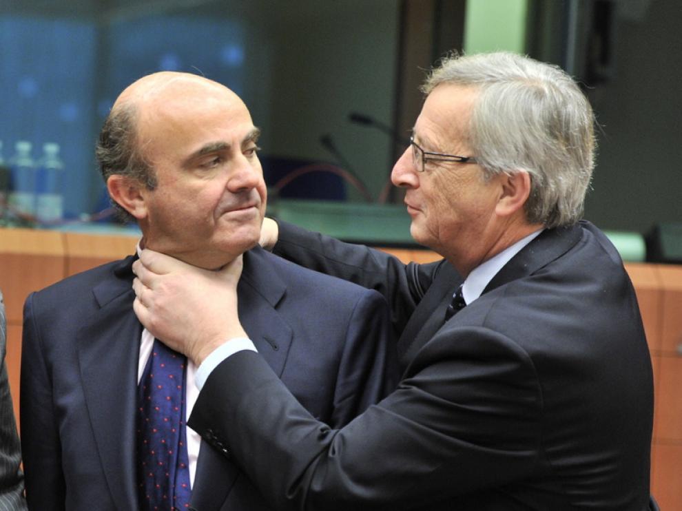 Jean-Claude Juncker y De Guindos bromean durante la reunión