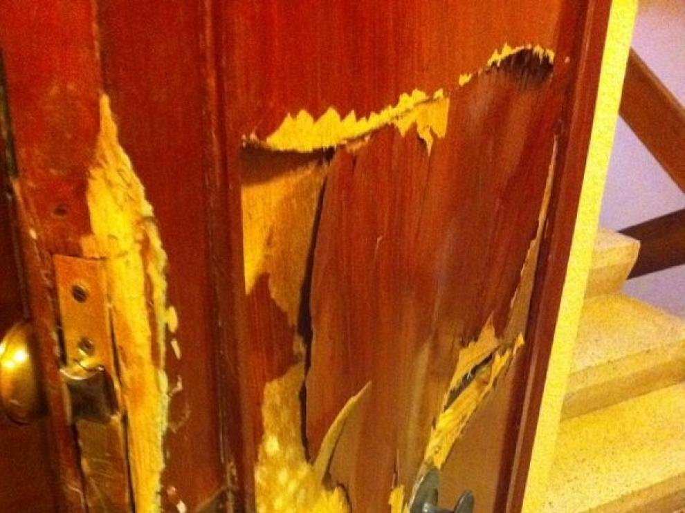 Aspecto de la puerta de una vivienda zaragozana tras ser reventada