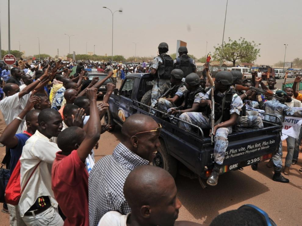 Partidarios de la Junta militar de Mali se concentran alrededor de un camión cargado con soldados.