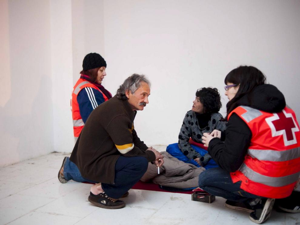 Voluntarios de la Cruz Roja ayudan a un sintecho