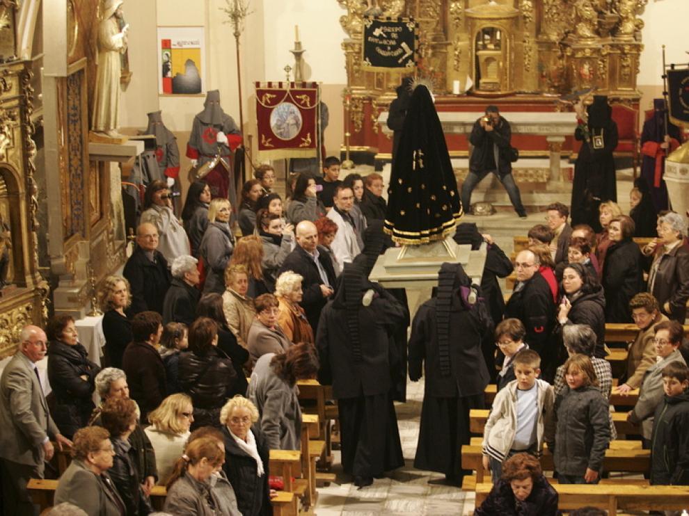 La virgen es llevada a hombros en el interior de la iglesia de Alcalá de Gurrea para protegerla de la lluvia.