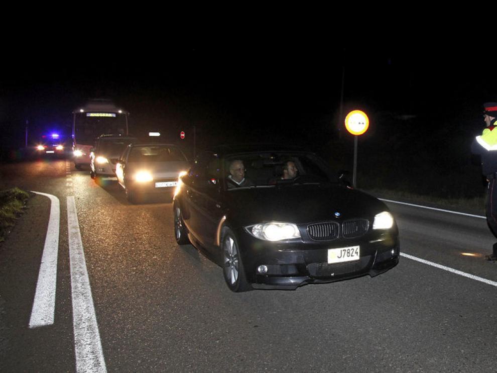 Un agente de los Mossos d'Esquadra dirige el tráfico en la carretera L-313, a su paso por Oliola.