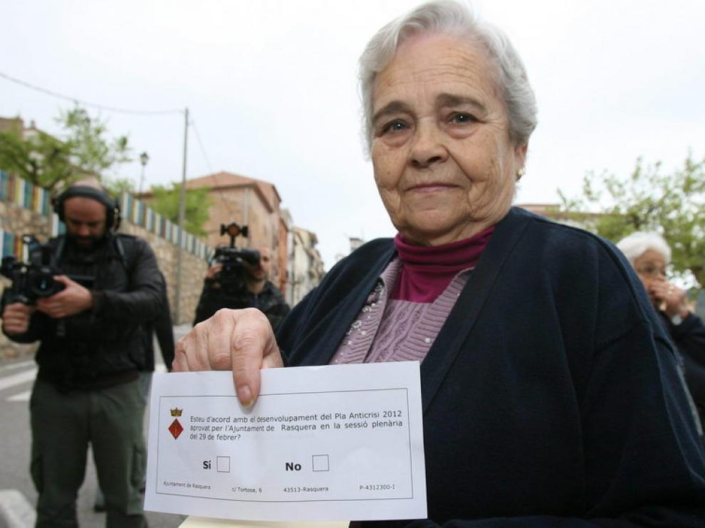 Una vecina muestra la papeleta para participar en el referendo.