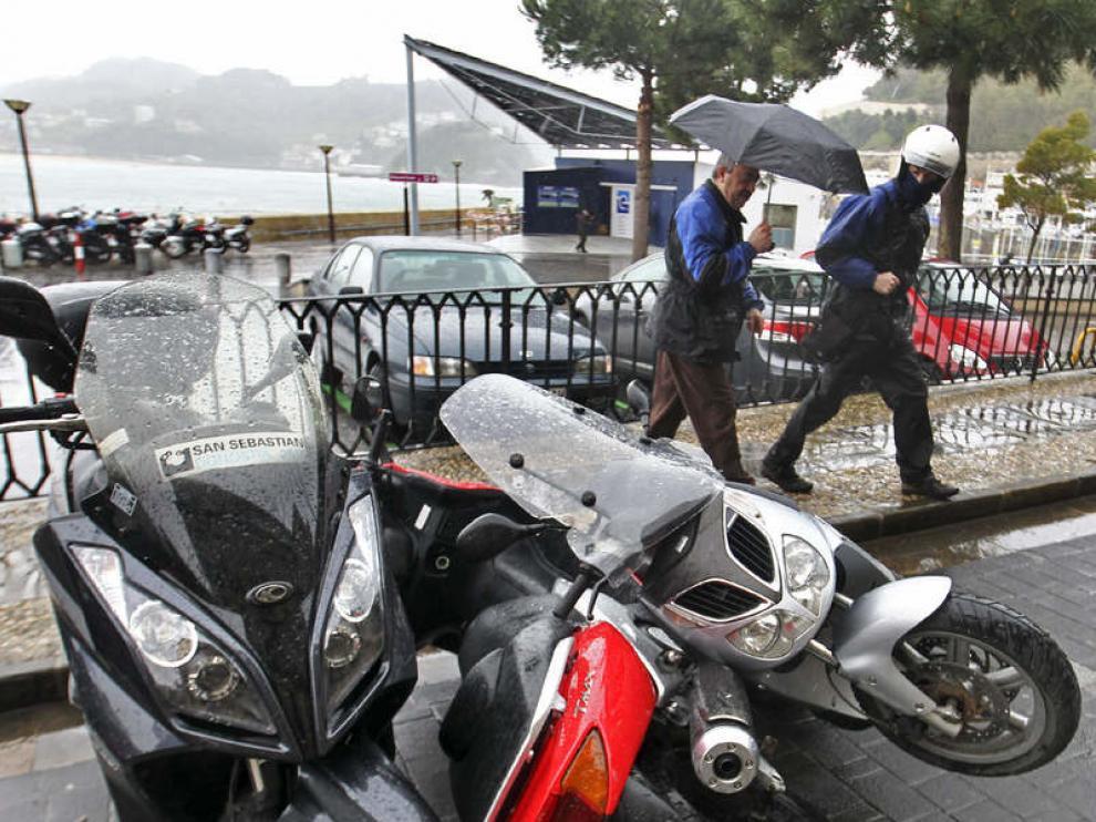 Dos conductores observan unos vehiculos derribados por el temporal en San Sebastián