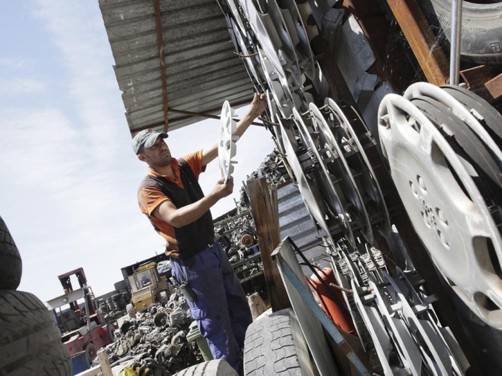 Un trabajador coloca los tapacubos en un desguace