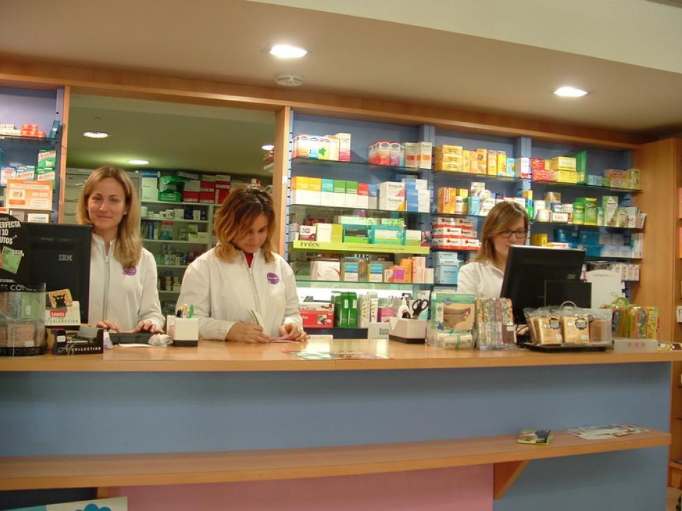 Raquel Ciriza, a la derecha de la imagen, tras el mostrador de su farmacia junto a dos empleadas