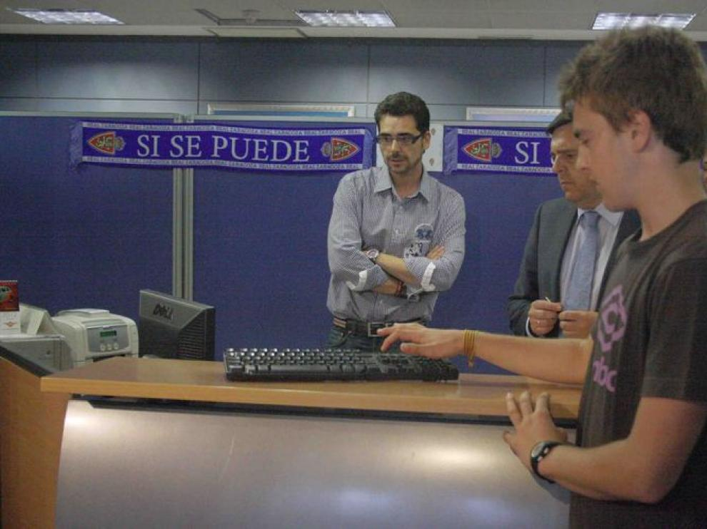 El voluntario, Julián Borque, pulsa el botón de inicio del sorteo.