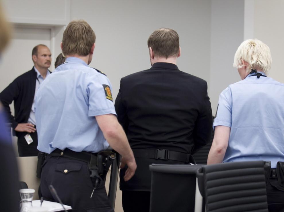 Breivi, este viernes, escoltado por dos policías durante el juicio