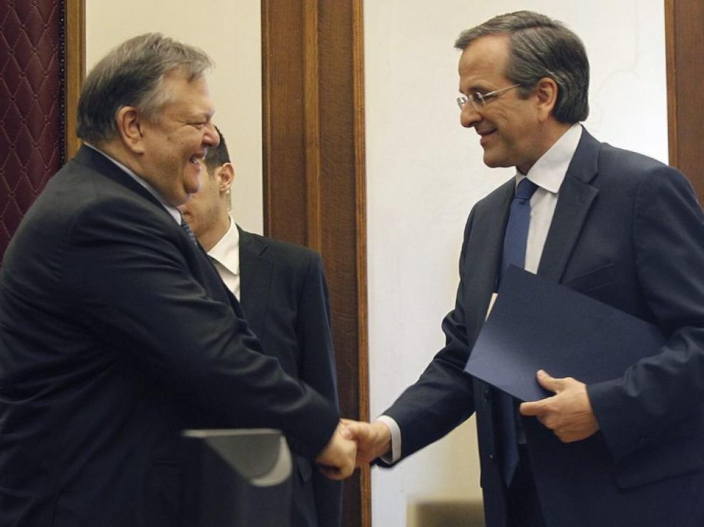 Evangelos Venizelos (izda) estrecha la mano de Antonis Samaras (dcha)