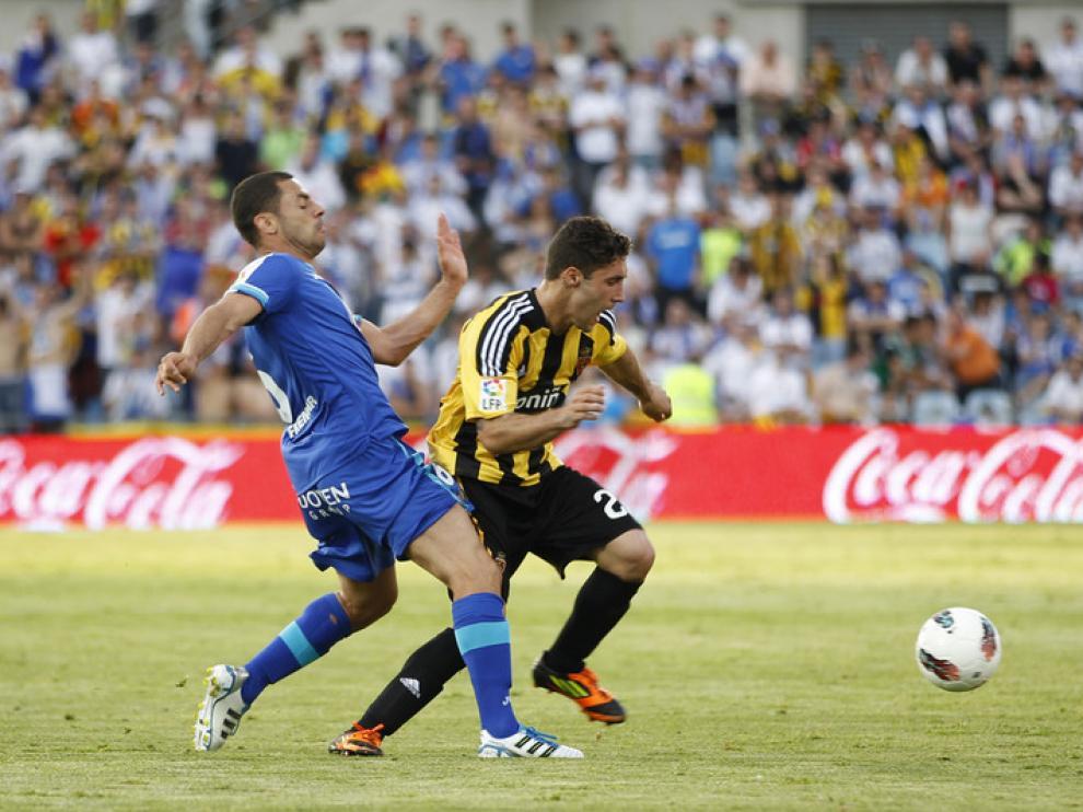 El defensa del Getafe CF Rafa López (d) pugna por el balón con el argentino Franco Zuculini