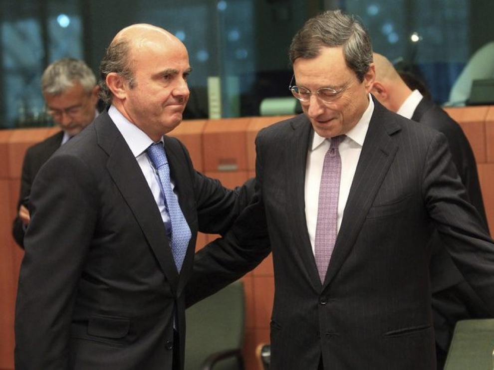 El ministro de Economía, Luis de Guindos (i), y el presidente del Banco Central Europeo, Mario Draghi