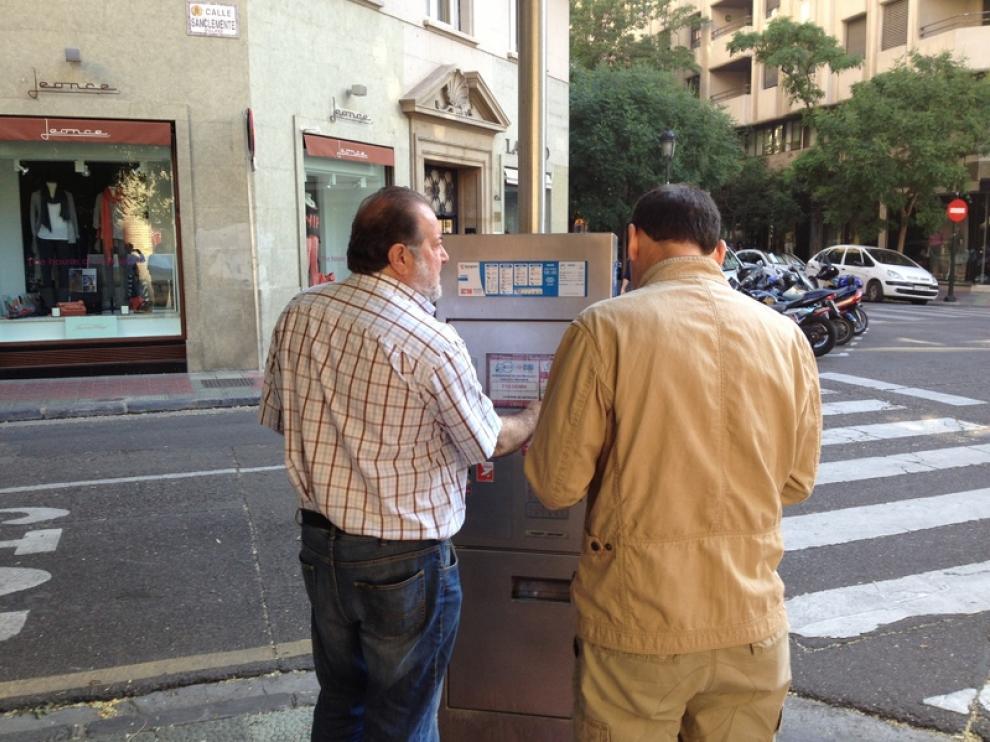 Dos personas intentando sacar el ticket del parquímetro