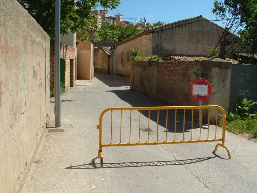 La entrada a la calle desde Ronda del Isuela presenta una valla de obra y una señal que informa del cierre al tráfico
