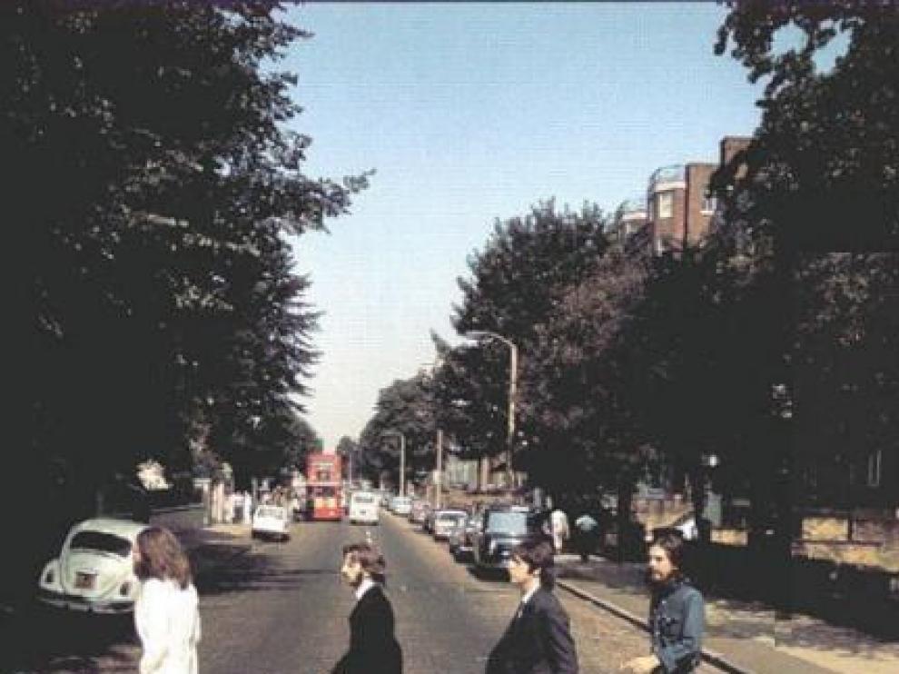 Los Beatles cruzando Abbey Road en sentido contrario a la portada del disco