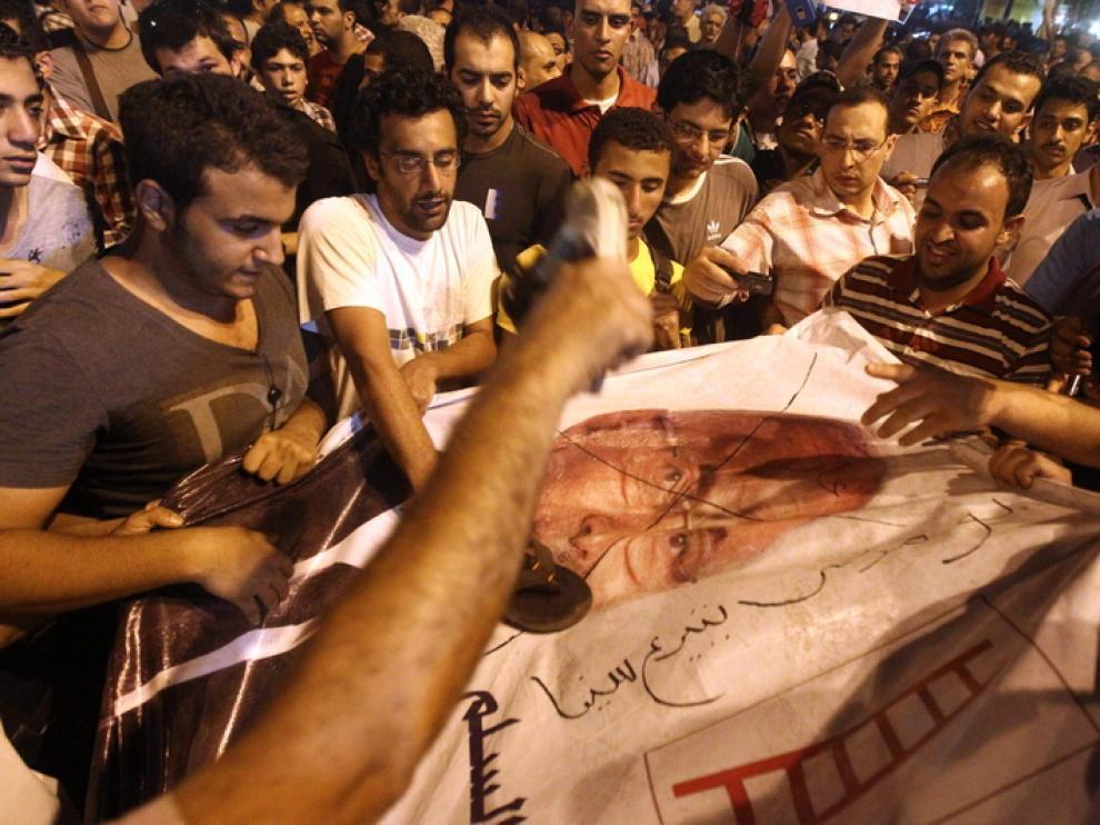 Los manifestantes pintan un cartel del candidato presidencial