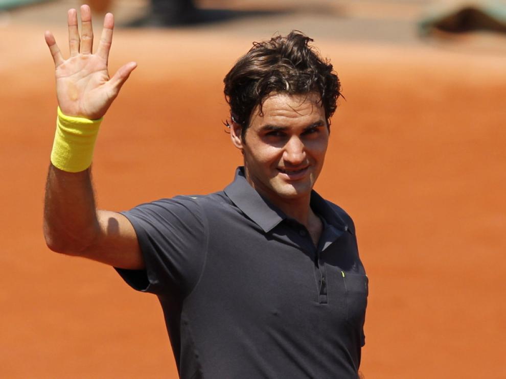 Roger Federer saluda al público tras conseguir su victoria 233 en Gran Slam