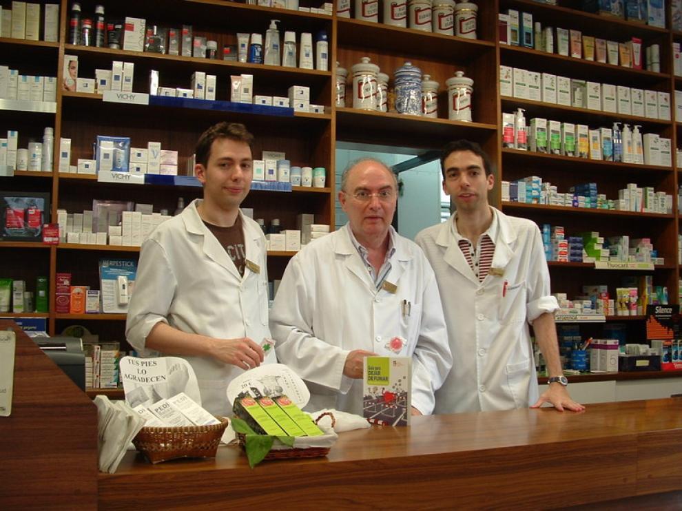 En la imagen, a la izquierda, Ignacio Compairé, junto a su padre y su hermano, muestran las piruletas y la Guía para dejar de fumar