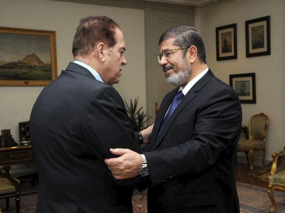 Mohamed Mursi (dcha), saludando al primer ministro saliente, Kamal Ganzouri