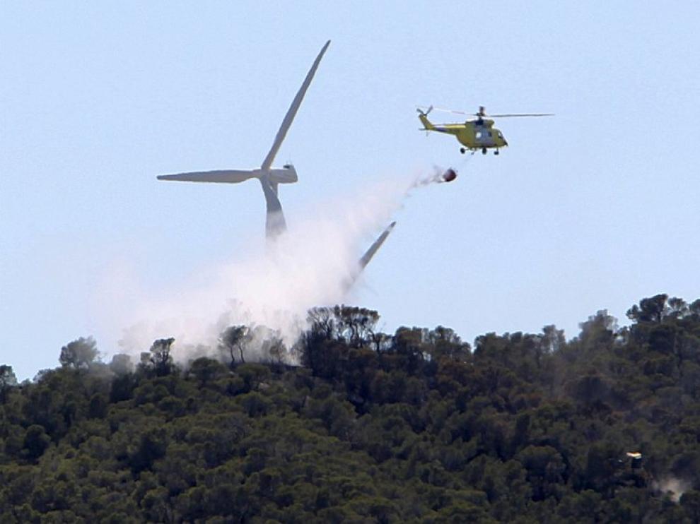 Un helicóptero descarga agua sobre el incendio