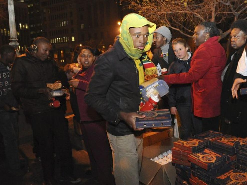Varias personas entregan mantas y alimentos a gente sin hogar para celebrar el Día Internacional de Mandela.