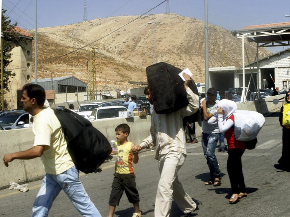 Familias sirias curzan la frontera libanesa con Siria.