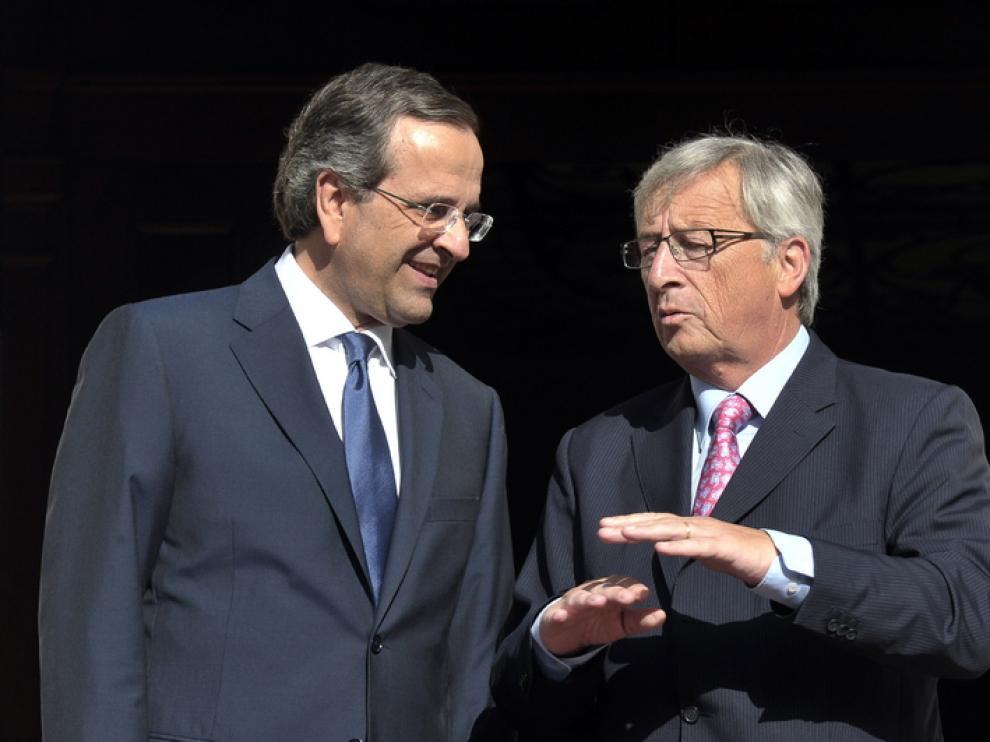 El primer ministro griego, Antonis Samaras, habla con Juncker, director del Eurogrupo