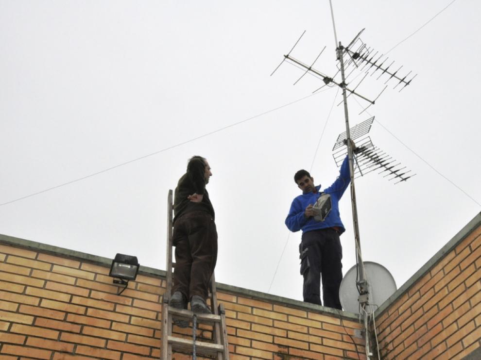 Unos técnicos ajustan la antena de televisión de una vivienda