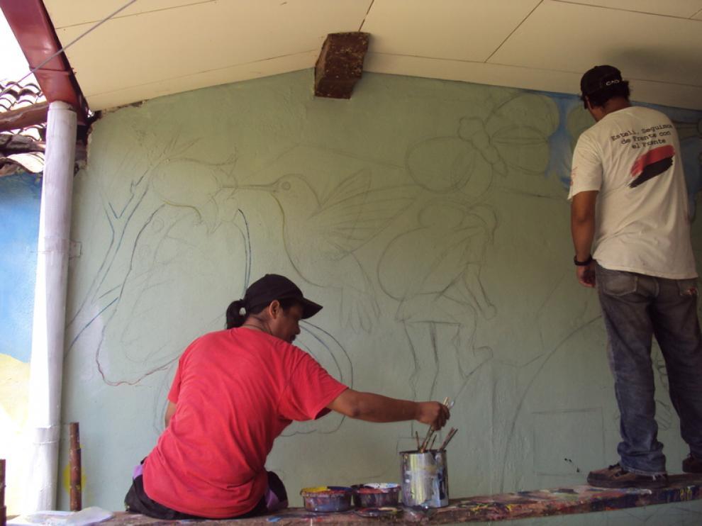 Unos jóvenes pintan un mural en León