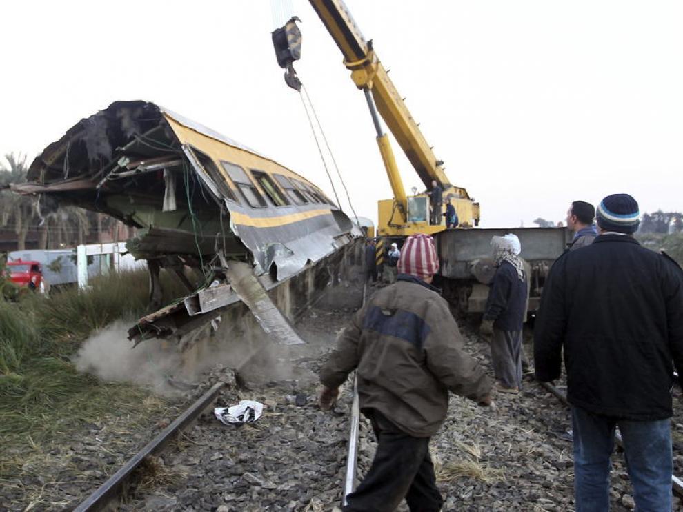 Miembros de los equipos de rescate levantan un vagón de tren tras un accidente en Guiza.