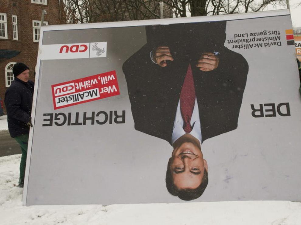 Dos operarios retiran el cartel del candidato de la CDU