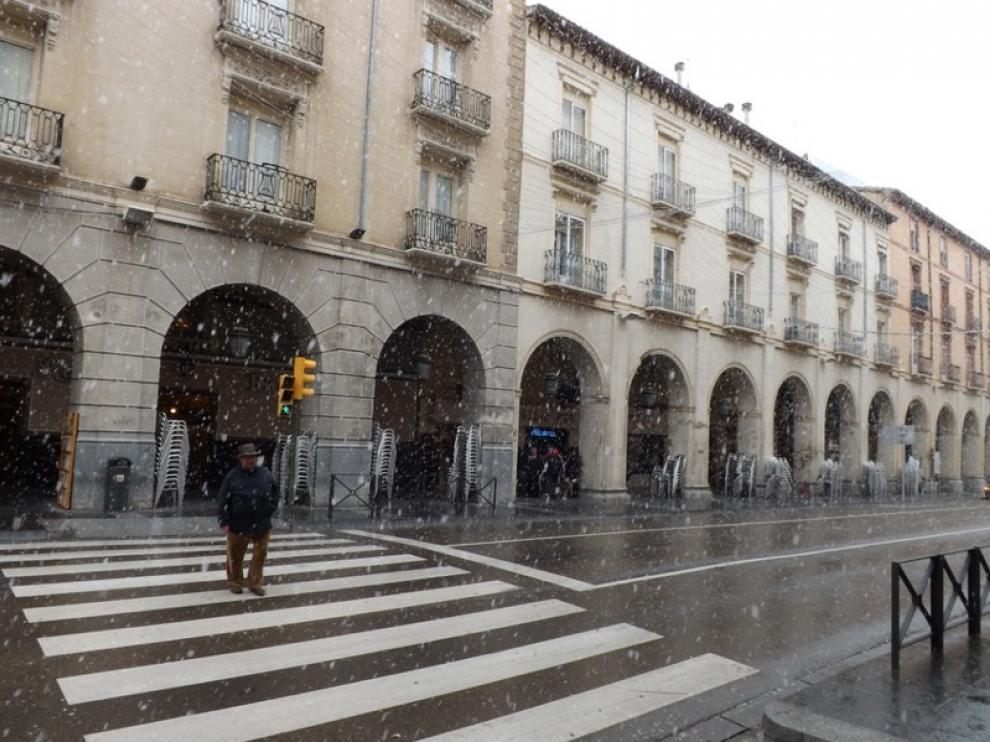 Este martes por la mañana, algunos copos sorprendían a los ciudadanos en Huesca