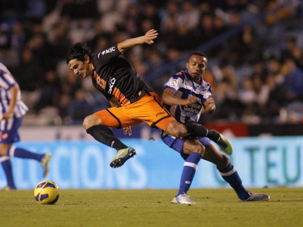 El centrocampista argentino del Valencia, Tino Costa , cae ante la entrada del defensa brasileño del Deportivo La Coruña, Paulo Asunsao