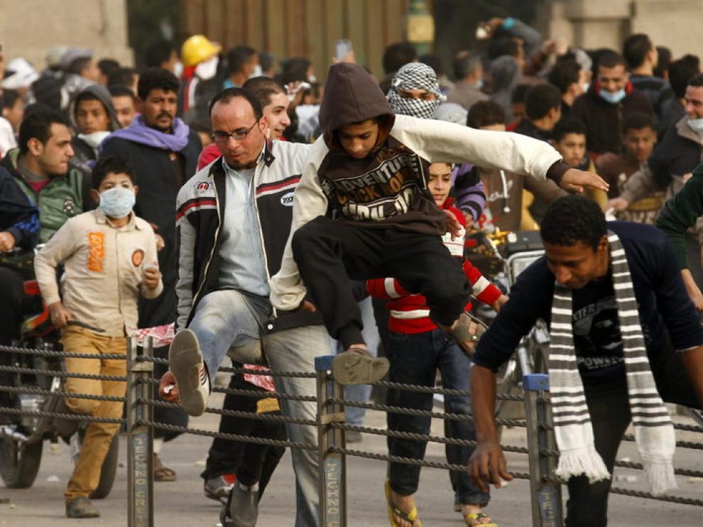 Protestantes egipcios huyendo de los gases lacrimógenos