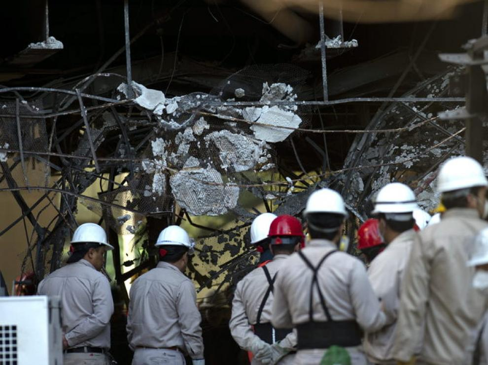 Empleados de Pemex observan los daños causados por la explosión