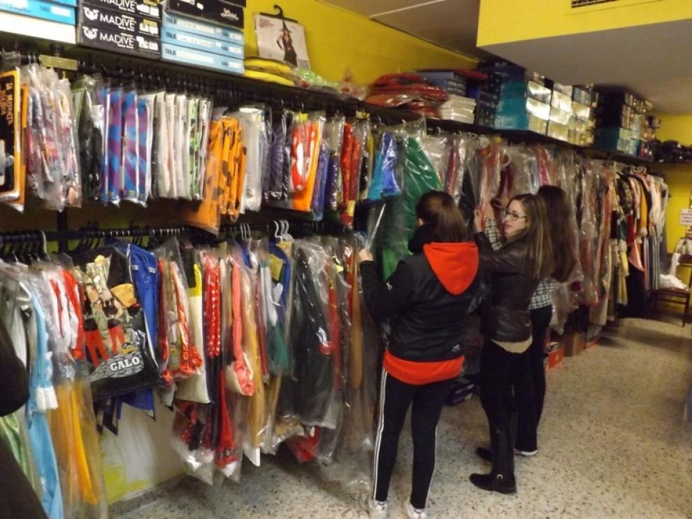 En la imagen, unas chicas mirando disfraces en la Pirotecnia Oscense