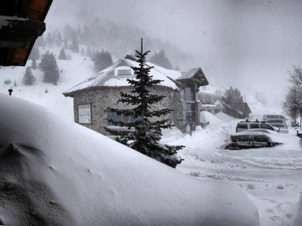 Coches de la Guardia Civil cubiertos por la nieve en Llanos del Hospital