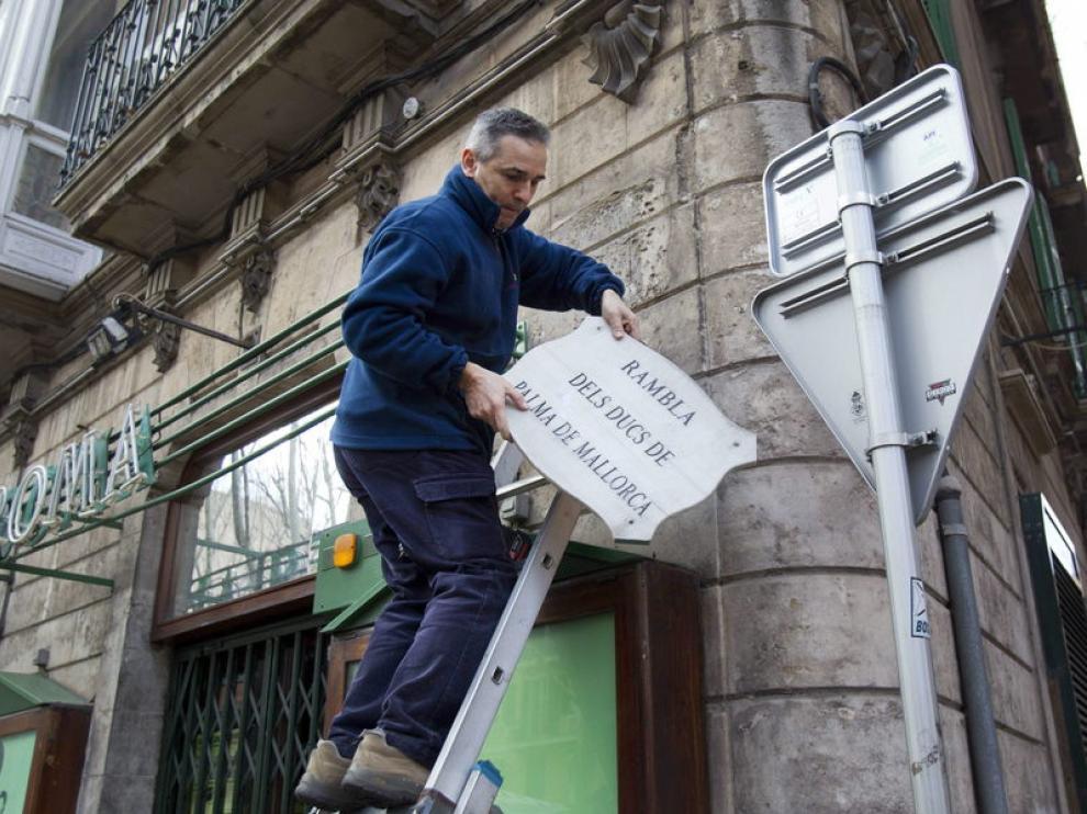 Un operario del Ayuntamiento retira la placa con el nombre antiguo de La Rambla