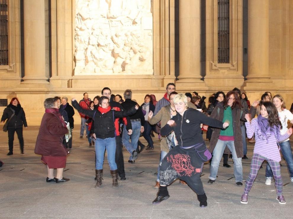 Activistas contra la violencia de género bailan en la plaza del Pilar