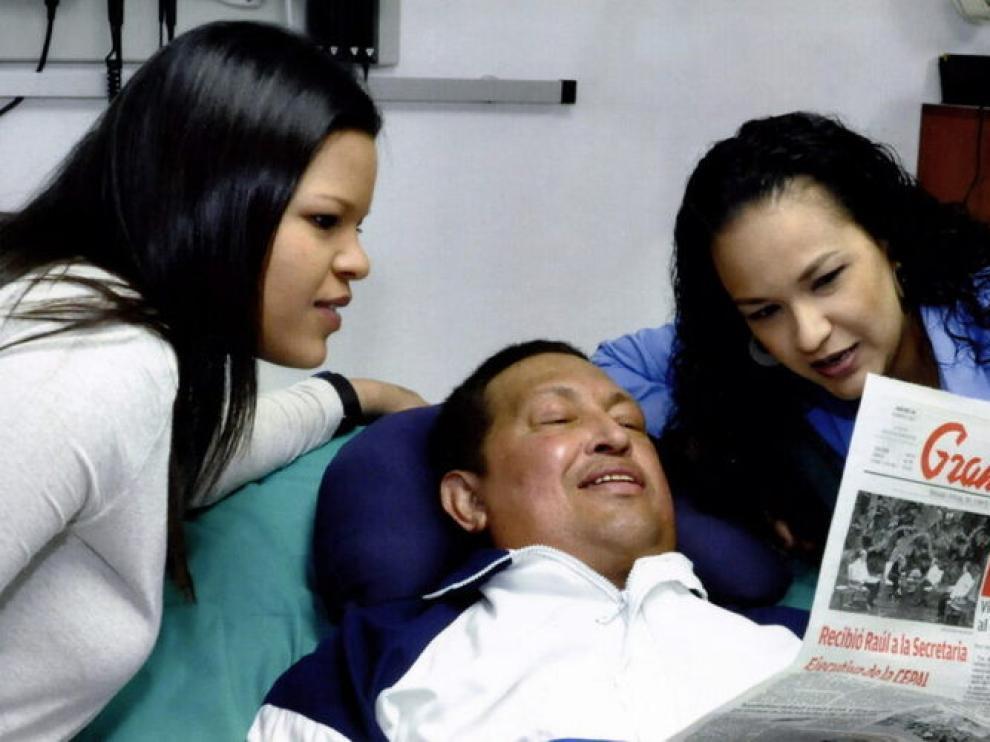 El presidente Chávez, junto a dos de sus hijas y un ejemplar del diario 'Gramna'