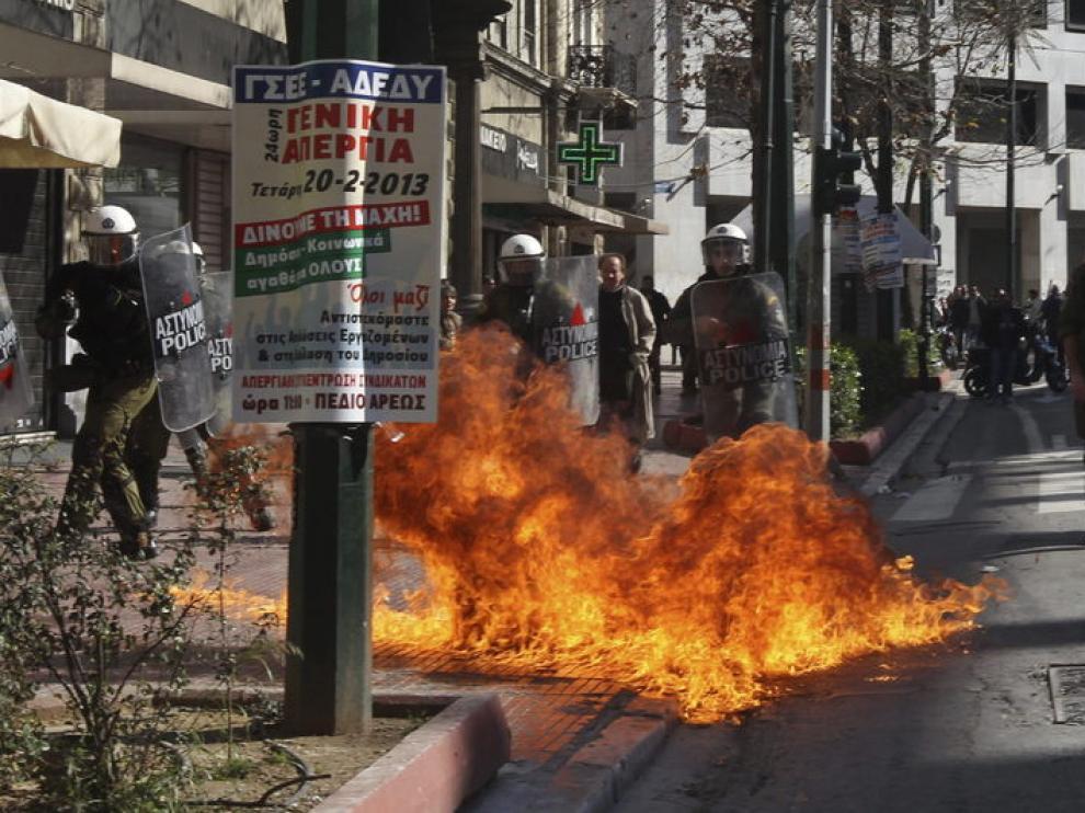 Agentes de policía antidisturbios, tras el lanzamiento de un cóctel molotov durante una manifestación frente al Parlamento griego