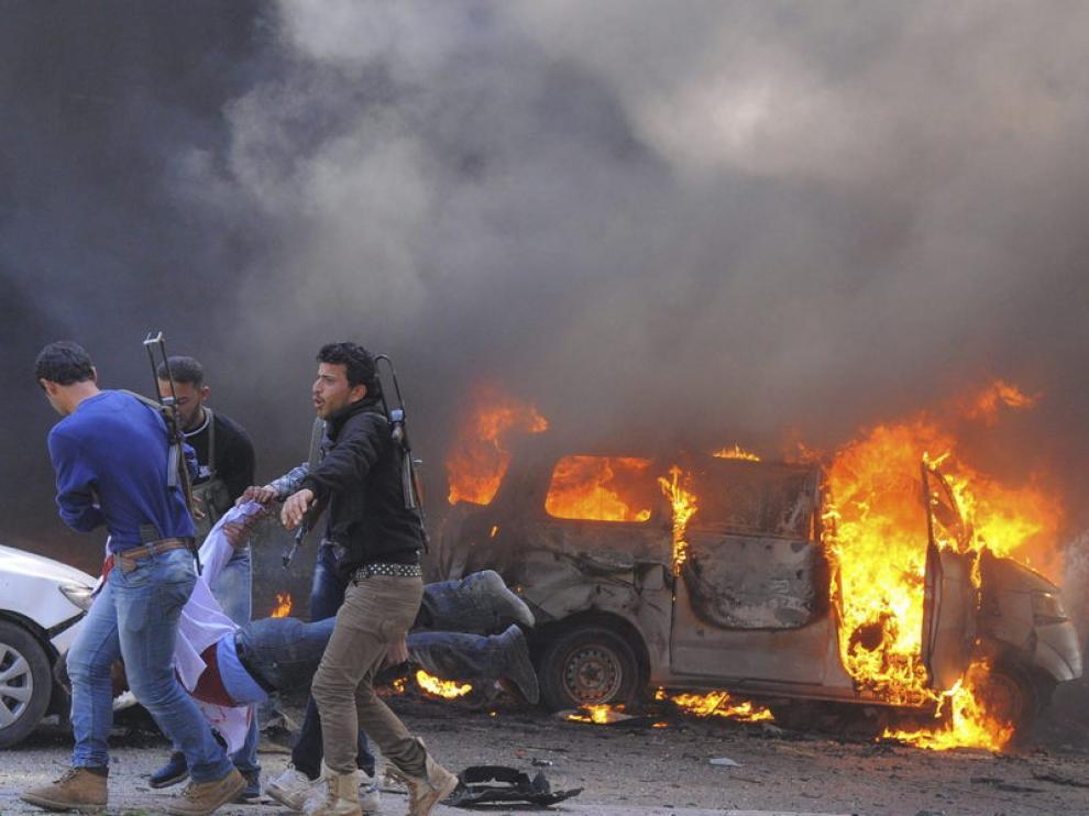 Tres rebeldes sirios llevan en volandas a un herido en el atentado en Damasco.