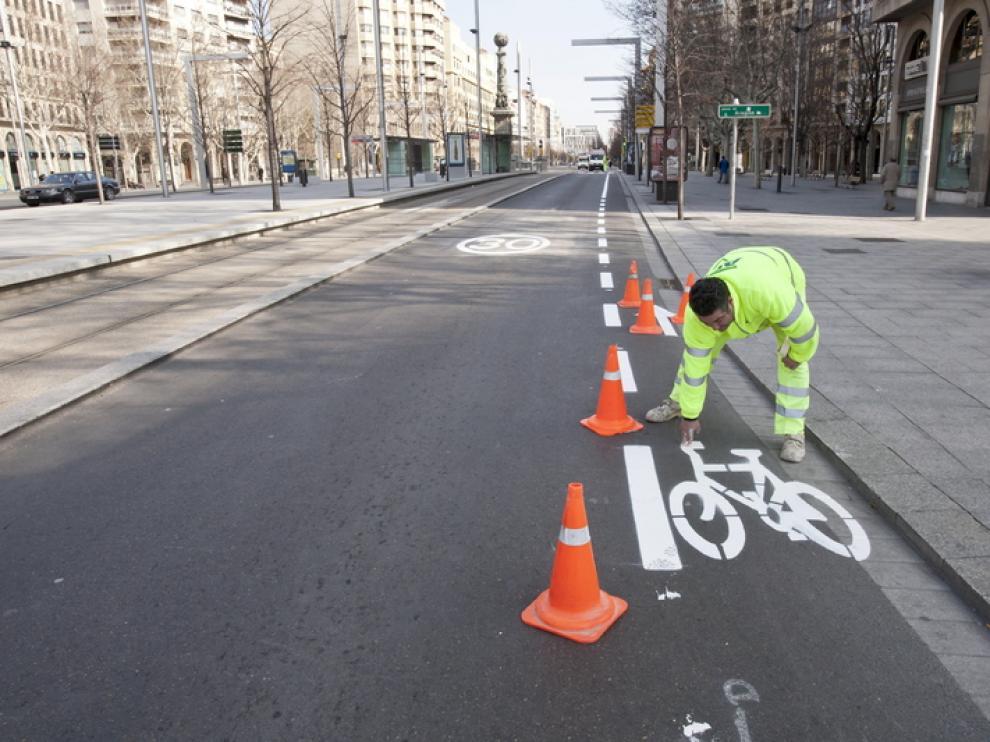 Un empleado pinta el carril bici en Independencia