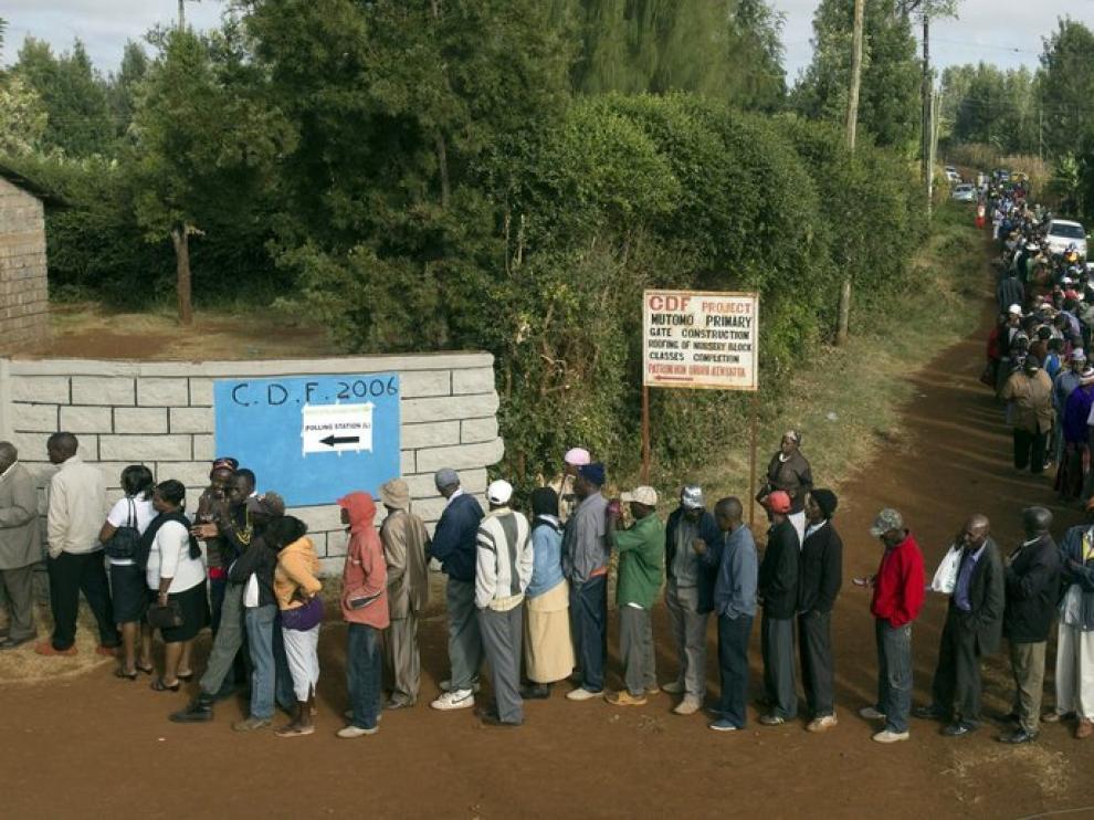 Una larga fila de votantes esperan su turno en uno de los colegios electorales