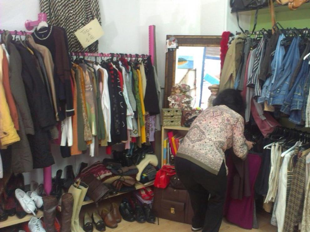 Pilar González, una voluntaria, arregla la ropa expuesta en la tienda.