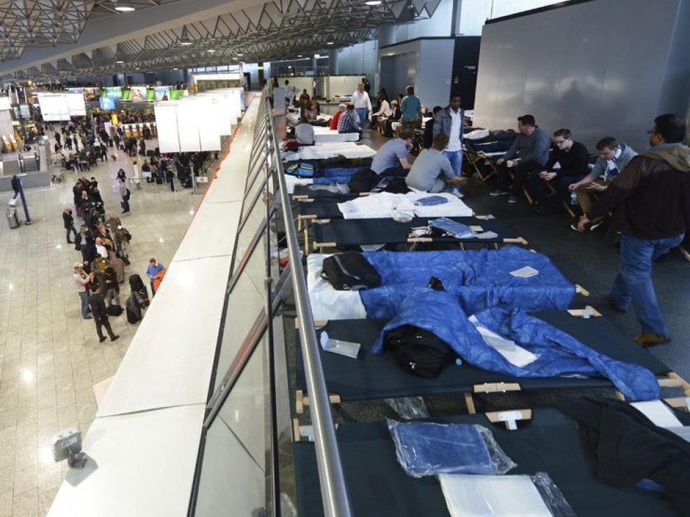 Varios pasajeros esperan en camas plegables en la Terminal 1.